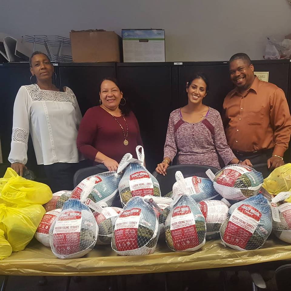 Four CAPCO staff and volunteers pose with the Thanksgiving dinners they brought in for our clients.