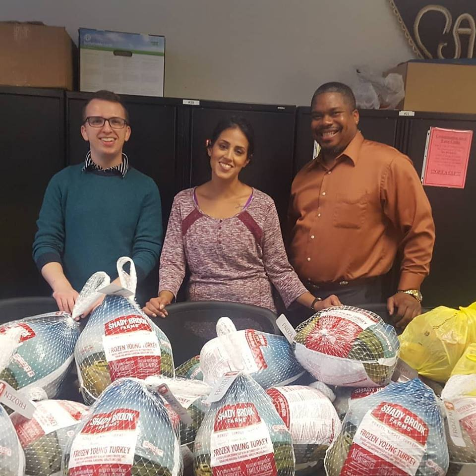 Three CAPCO staff and volunteers pose with the Thanksgiving dinners donated by St. Luke Baptist Church for CAPCO clients.